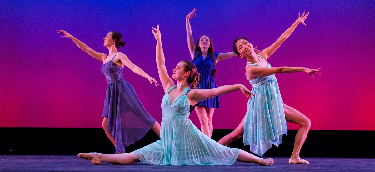 Four women in blue dresses dancing in front of gradient background
