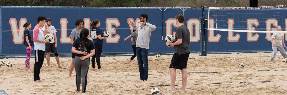 Students on sand court during volleyball class