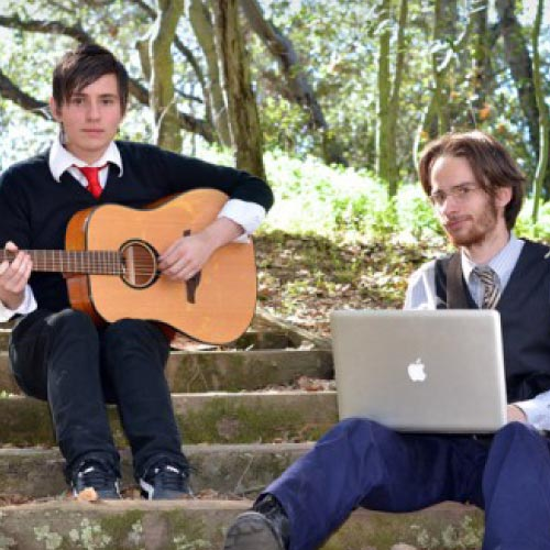 Two music students on stairs guitar and laptop
