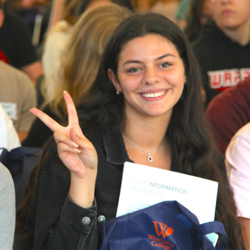 Female student giving peace sign