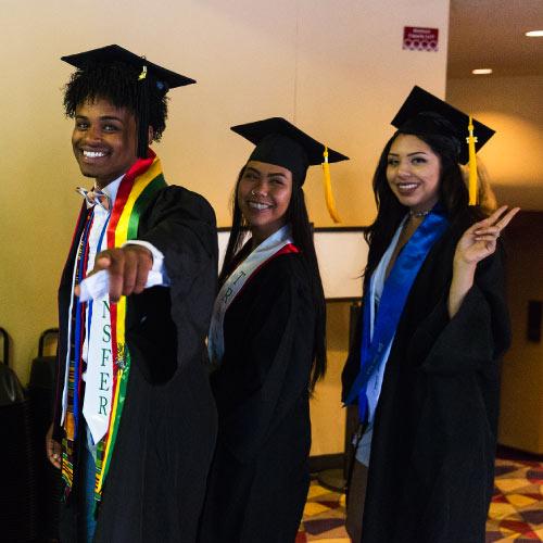 Three graduates waving at camera