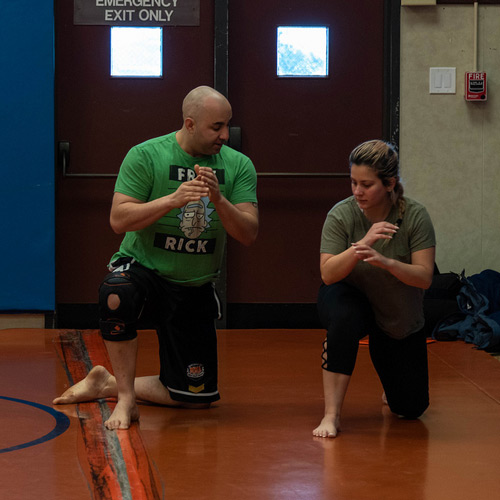 Instructor guiding student in combat class