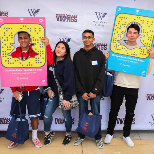 Students with Snapchat props in front of step and repeat