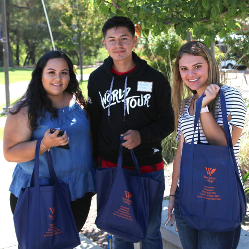 Three students with West Valley swag bags during Convocation