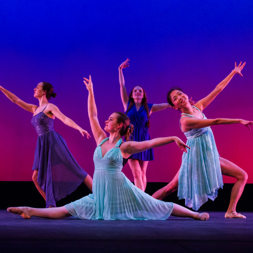 Students in blue dresses in dance pose in front of gradient background