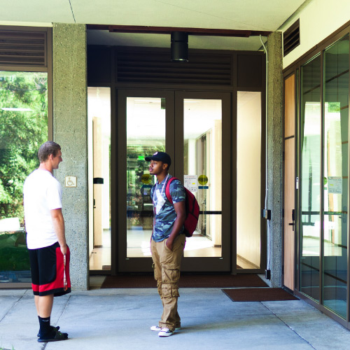 Two students conversing in front of the Language Arts and Social Science building